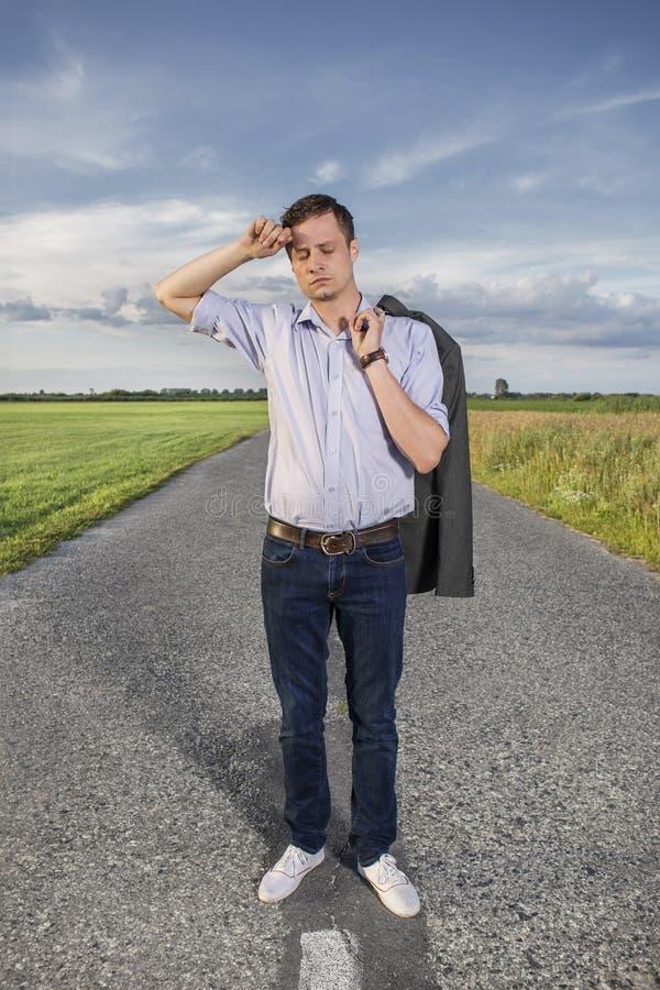 Intégral du jeune homme fatigué se tenant sur la route rurale vide photographie stock