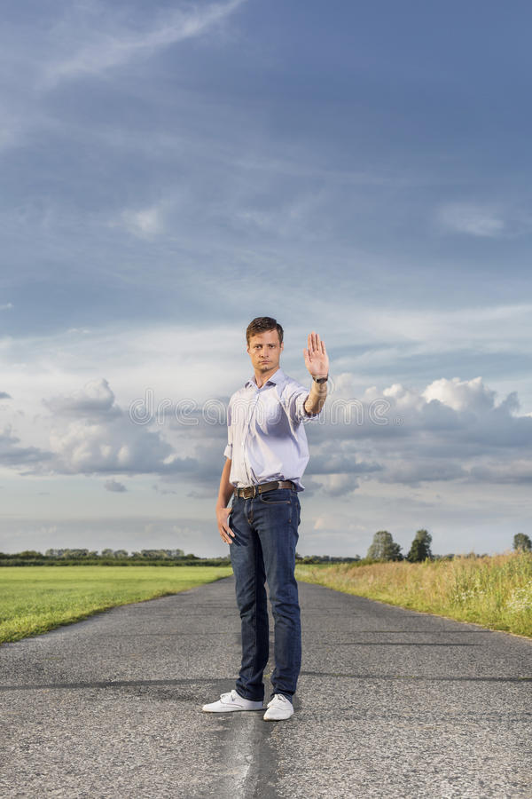 Intégral du jeune homme sérieux retardant la main pour s'arrêter à la route de campagne image libre de droits