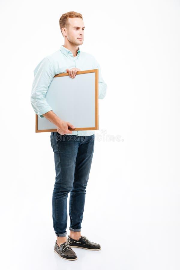 Intégral du jeune homme sérieux tenant et tenant le tableau blanc photos libres de droits
