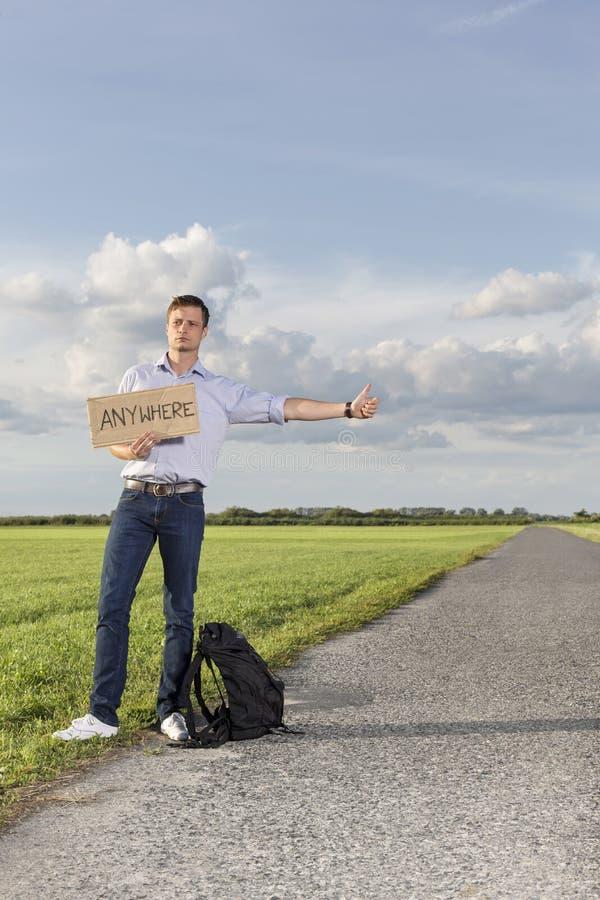 Intégral du jeune homme s'accrochant tout en se tenant n'importe où connectez-vous la campagne photo stock