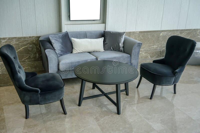 Intérieur à la maison avec la table de cercle noire, les chaises noires et le sofa gris images libres de droits
