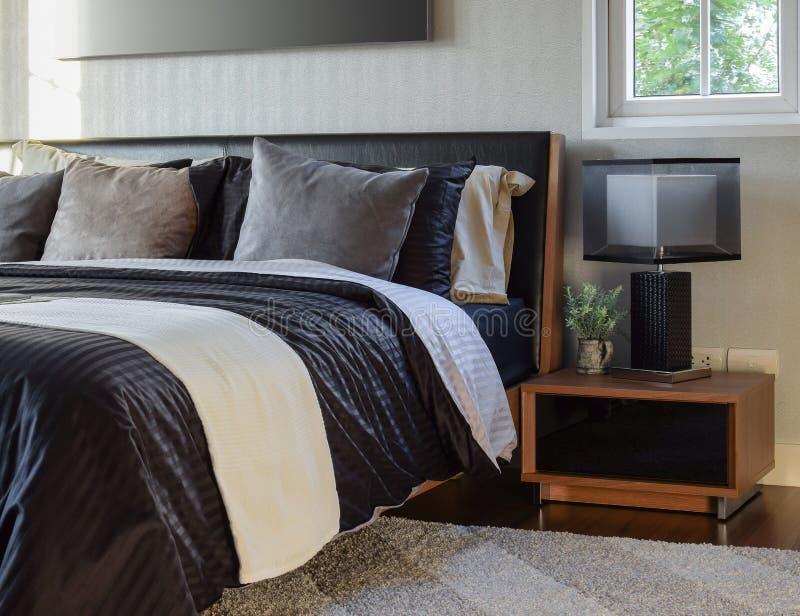 Intérieur élégant de chambre à coucher avec la lampe moderne de table de chevet images stock