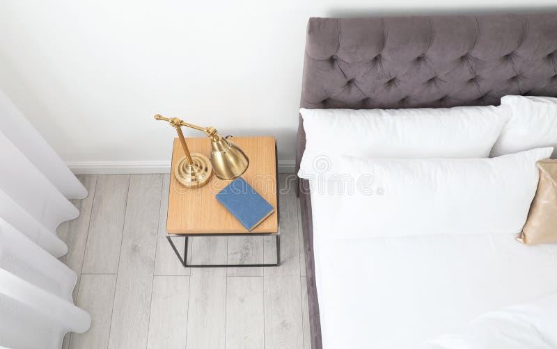 Intérieur élégant de pièce avec le lit et le nightstand confortables images stock