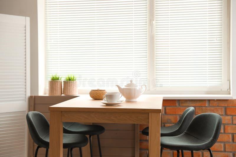 Intérieur élégant de salle à manger avec des abat-jour d'ensemble et de fenêtre de table photographie stock libre de droits