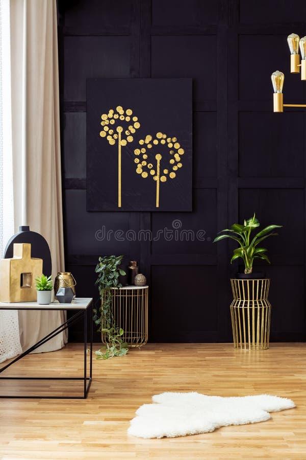 Intérieur élégant de salon avec des accents d'or, peignant sur un mur noir photos libres de droits
