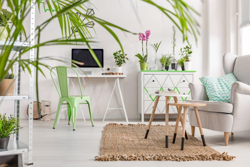 Intérieur avec un bureau blanc, une chaise en bon état, un coffre des tiroirs et un fauteuil photos libres de droits