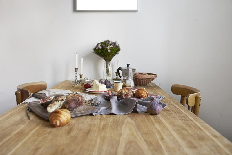 Intérieur blanc de cuisine avec le petit déjeuner de la Provence sur la table en bois, affiche sur le mur blanc, l'espace pour la image stock
