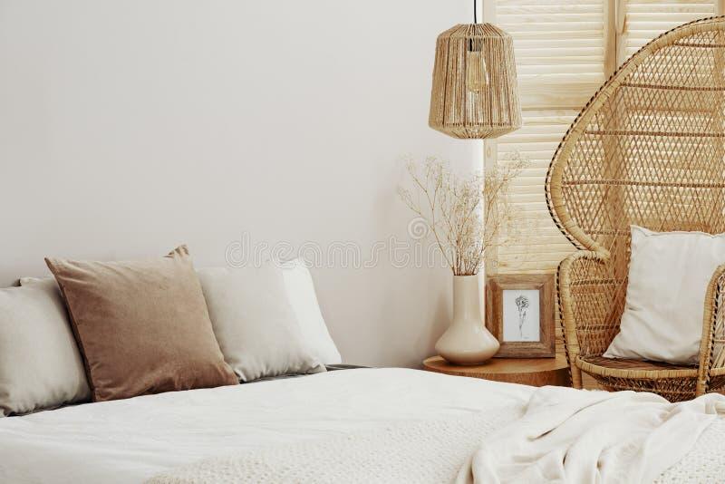 Intérieur blanc et lumineux avec la chaise de paon et la lampe en osier de rotin image stock