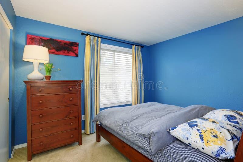 Intérieur bleu d'une petite chambre à coucher avec la raboteuse brune photo stock