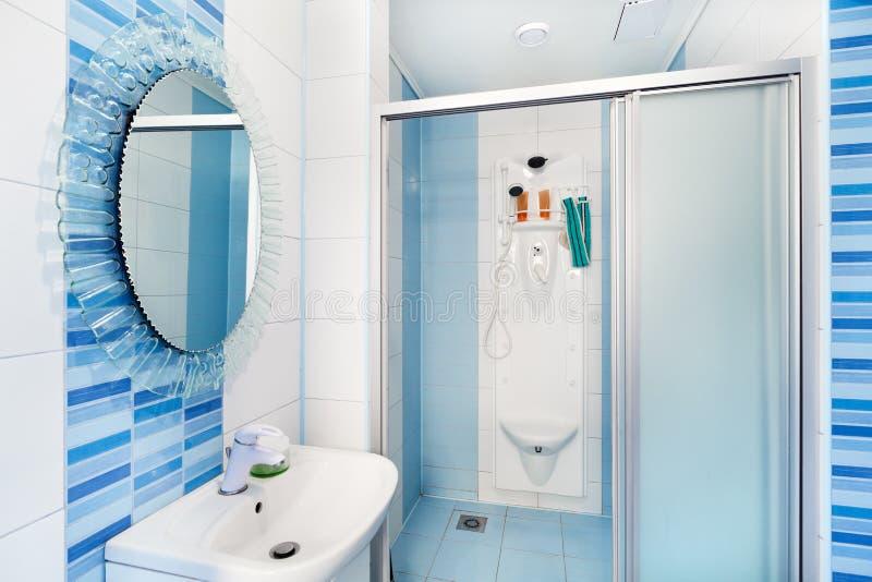Intérieur bleu moderne de salle de bains avec le miroir rond photos stock