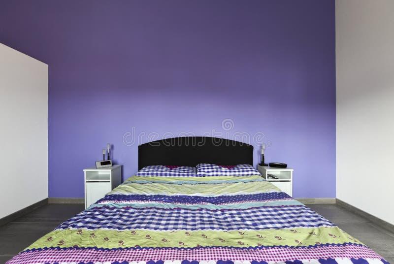 Intérieur, chambre à coucher avec le mur pourpré photographie stock libre de droits