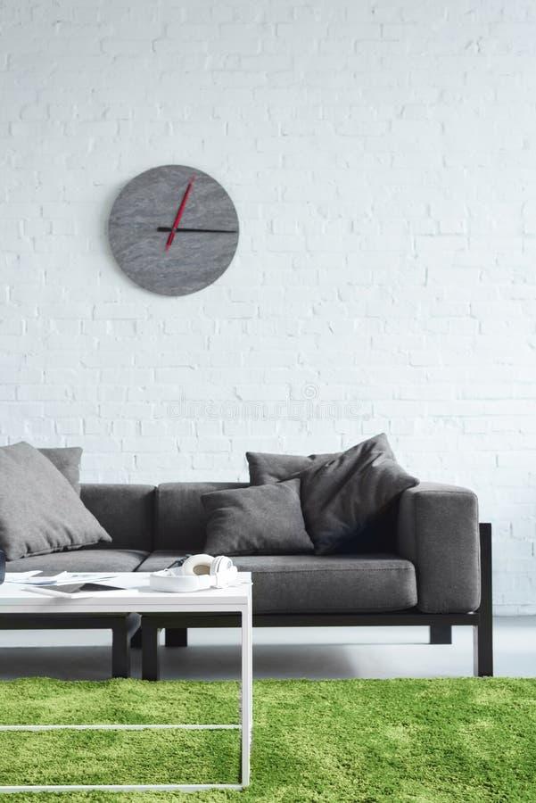 Intérieur confortable avec le sofa et l'horloge gris modernes photographie stock libre de droits