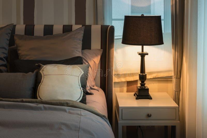 Intérieur confortable de chambre à coucher avec les oreillers de brun foncé et la lampe de lecture photos stock