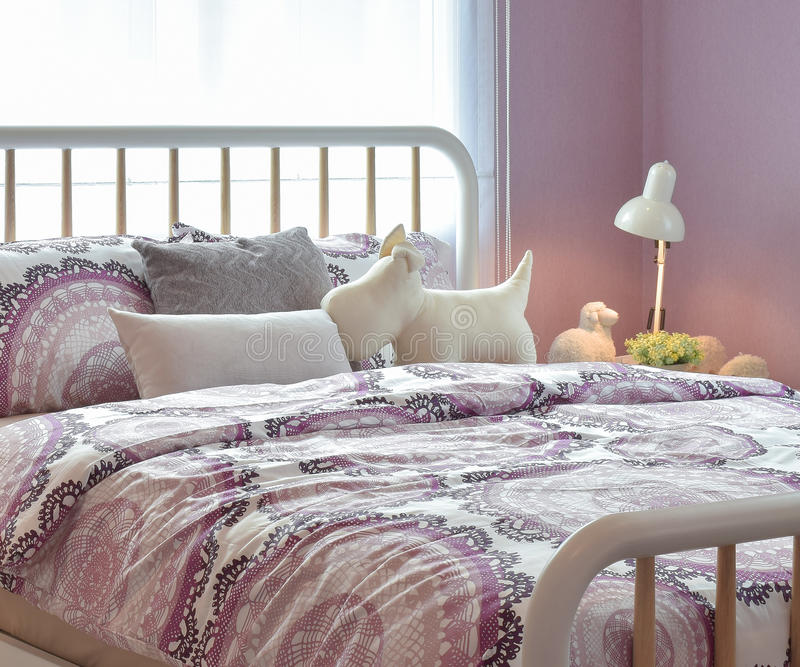 Intérieur confortable de chambre à coucher avec les oreillers et la lampe de lecture sur la table de chevet image libre de droits