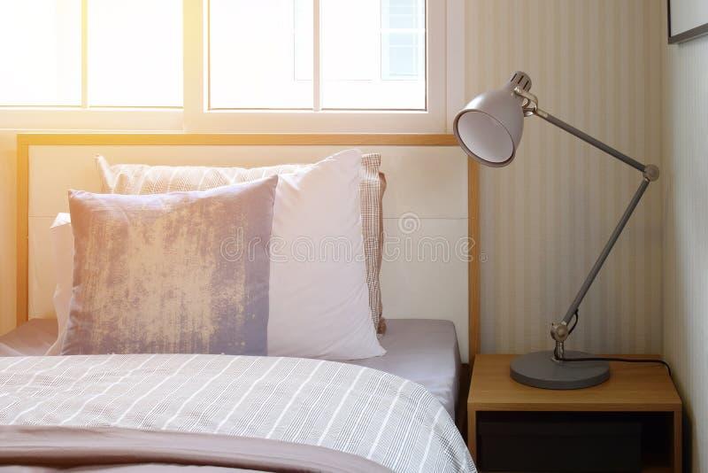 Intérieur confortable de chambre à coucher avec les oreillers et la lampe de lecture sur la table de chevet photos stock