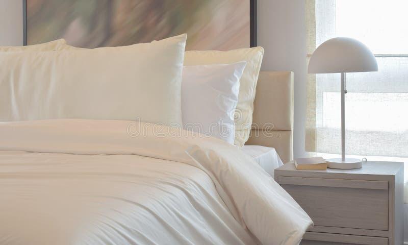 Intérieur confortable de chambre à coucher avec les oreillers et la lampe de lecture sur le chevet t photographie stock