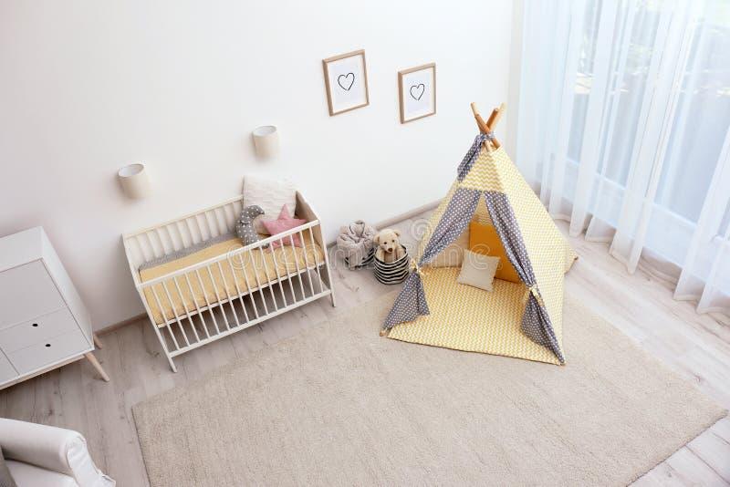 Intérieur confortable de pièce de bébé avec la tente et les jouets de jeu photographie stock libre de droits