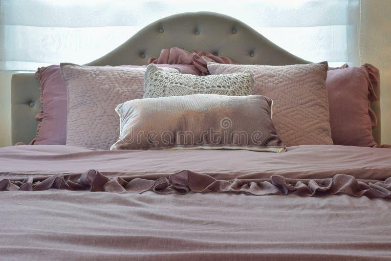 Intérieur confortable et classique de chambre à coucher avec les oreillers et la lampe de lecture sur la table de chevet image stock