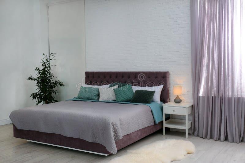 Intérieur contemporain de pièce avec le lit confortable photographie stock libre de droits