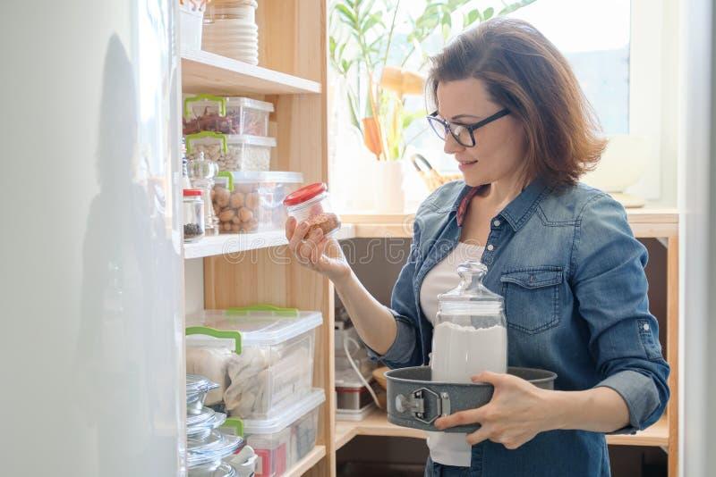 Intérieur d'office en bois avec des produits pour la cuisson Femme adulte prenant la vaisselle de cuisine et la nourriture image libre de droits