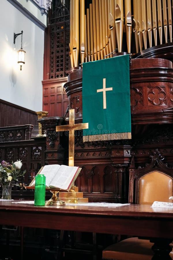 Intérieur d'un autel d'église protestante avec la croix, la Sainte Bible et les bougies d'or là-dessus photographie stock