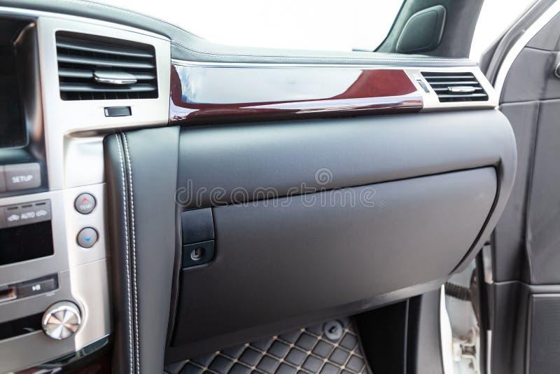 Intérieur d'une voiture de luxe avec piquer excessif intérieur en cuir sous forme de diamant du fil blanc à la boîte à gants de v image stock