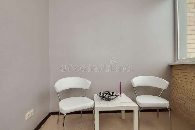 Intérieur de balcon avec la table blanche et chaises près du mur et de la fenêtre clairs vides gris photo stock