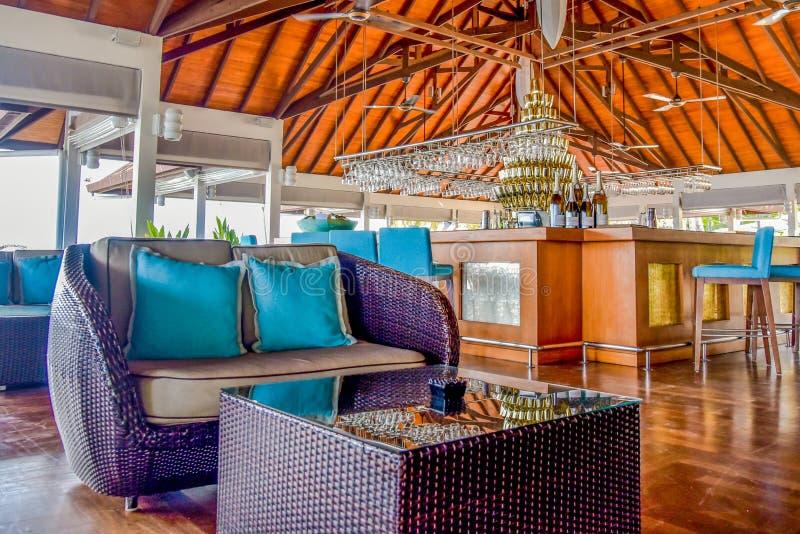 Intérieur de barre avec des tables et des chaises à la station de vacances tropicale image libre de droits