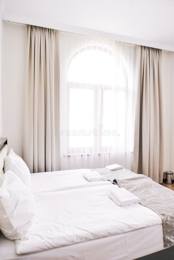 Intérieur de chambre à coucher dans les tons de lumière et de sable, le lit et la fenêtre photo stock