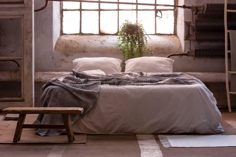 Intérieur de chambre à coucher de sabi de Wabi avec un lit, une usine et un tabouret en bois dans l'avant image libre de droits
