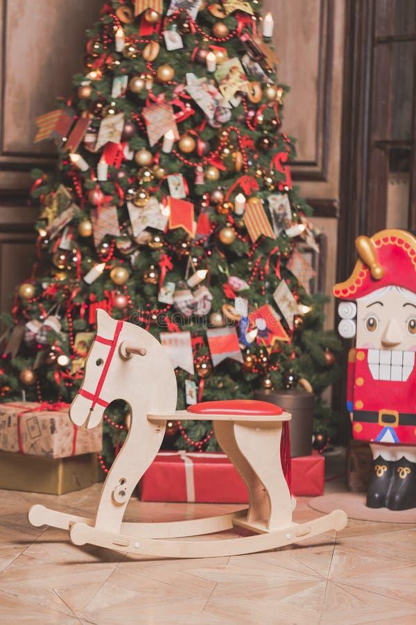 Intérieur de décoration de pièce de Noël avec la chaise de cheval, l'arbre de nouvelle année et le casse-noix Effet modifié la to photo stock