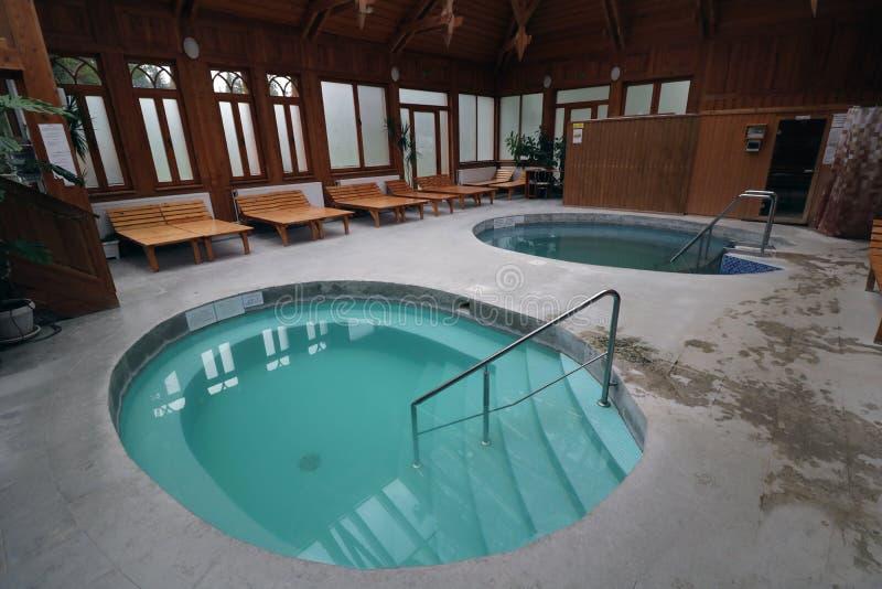 Intérieur de luxe de station thermale avec les piscines, l'eau bleue, les murs en bois et les chaises longues photo stock