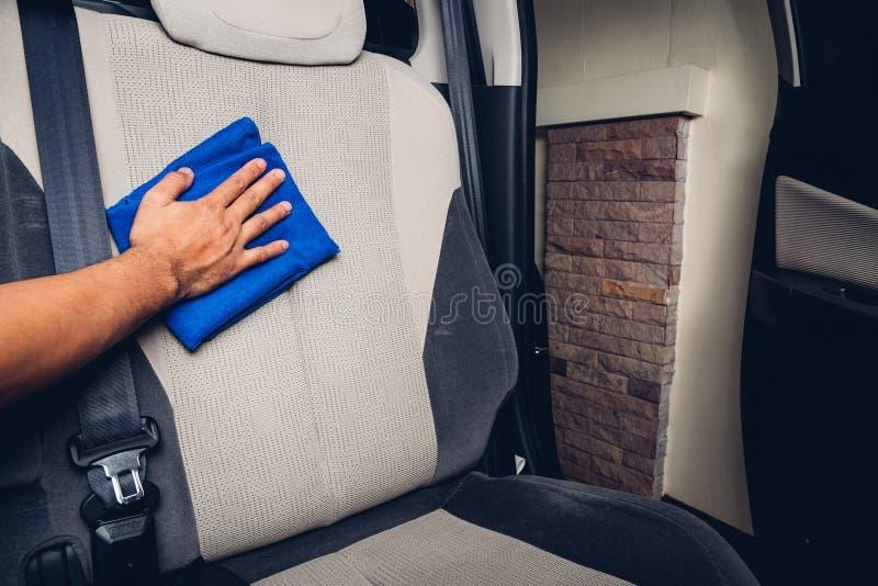 Intérieur de nettoyage de la poussière d'homme de travailleur par le microfiber de tissu à l'intérieur de la voiture image libre de droits