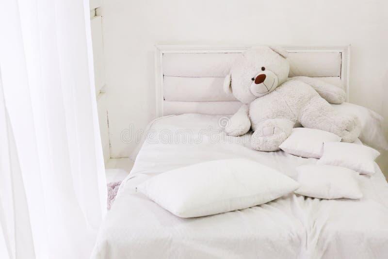 Intérieur de pièce blanche avec le lit, la fenêtre, les oreillers et l'ours photographie stock