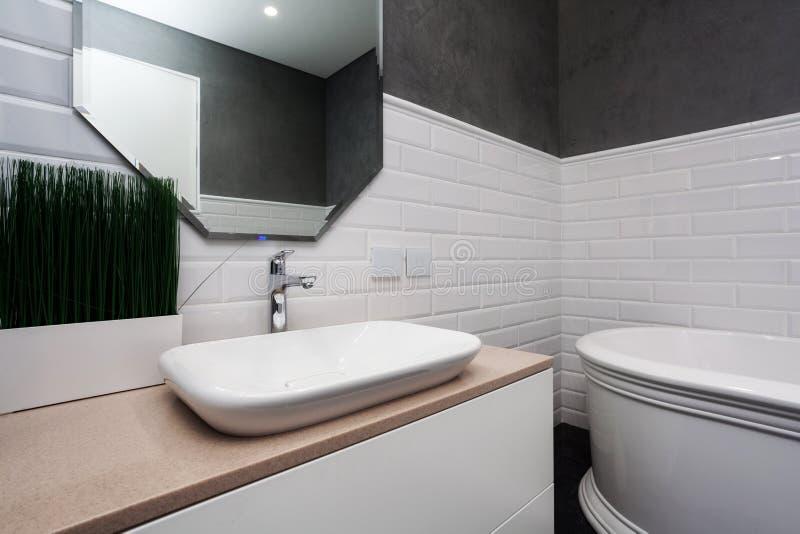 Intérieur de salle de bains Salle de bains lumineuse avec de nouvelles tuiles Nouveau lavabo, évier blanc et grand miroir images libres de droits