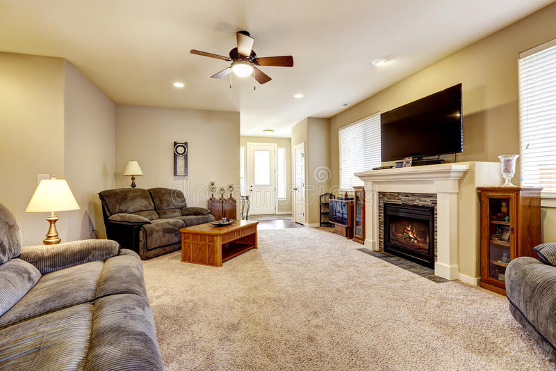 Intérieur de salon dans le style américain classique avec les murs beiges, l'ensemble gris de sofa et la cheminée images stock