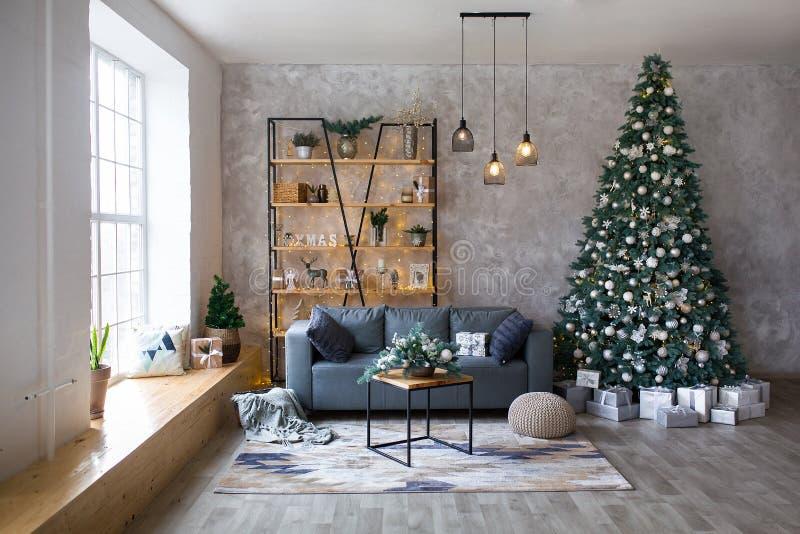Intérieur de salon moderne avec le sofa confortable décoré de l'arbre et des cadeaux de Noël photographie stock libre de droits