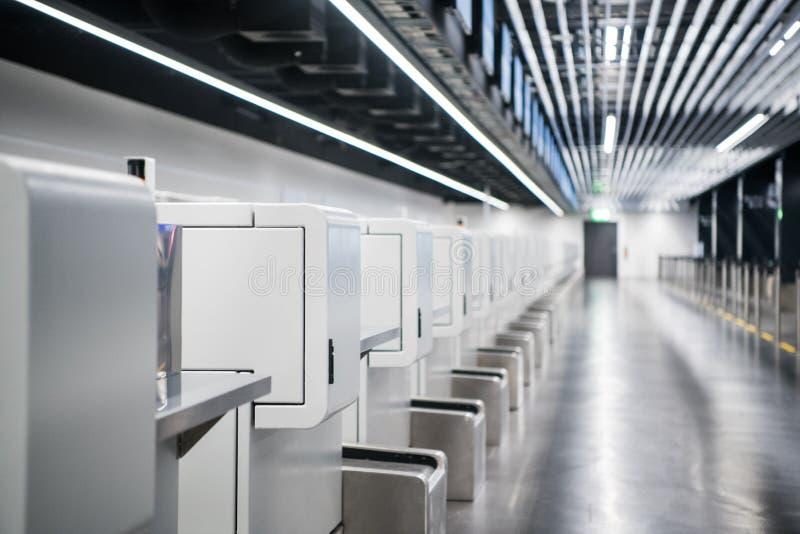Intérieur de secteur d'enregistrement dans l'aéroport moderne : le bagage acceptent des terminaux avec des bagages manipulant des photos stock