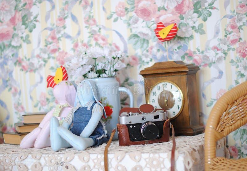 Intérieur doux de cru Appareil-photo, jouets de tilde, pile de livres et une bouilloire avec des marguerites de fleurs photos libres de droits