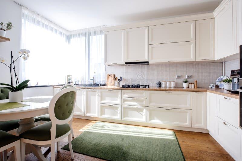 Intérieur merveilleux de cuisine avec la lumière naturelle et les meubles en bois modernes Planchers en bois dur et appareils mod photos libres de droits
