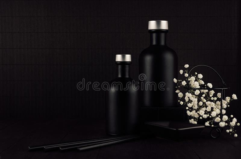 Intérieur minimaliste de noir foncé avec les bouteilles noires vides, petites fleurs blanches sur le panneau en bois foncé, moque photo stock
