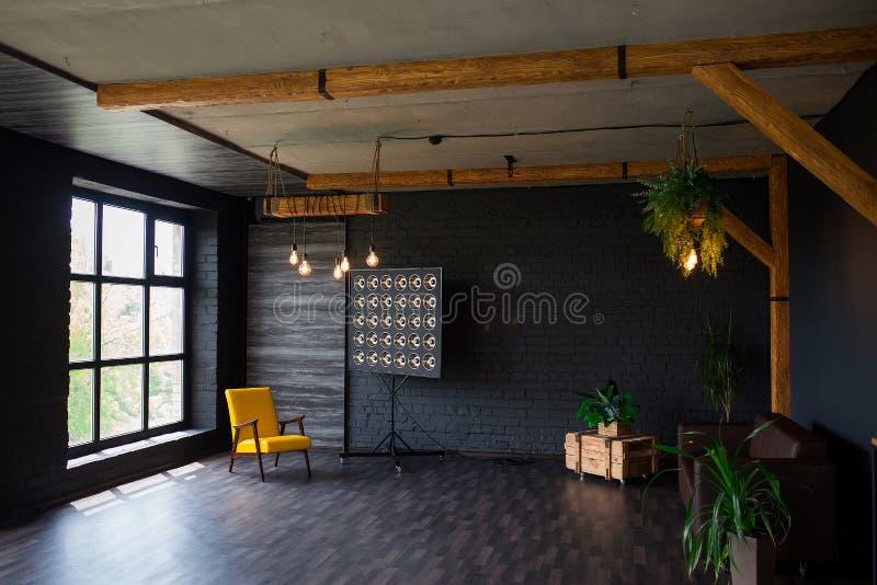 Intérieur moderne brutal dans une couleur foncée avec un sofa en cuir et une grande fenêtre Salon de style de grenier photos libres de droits
