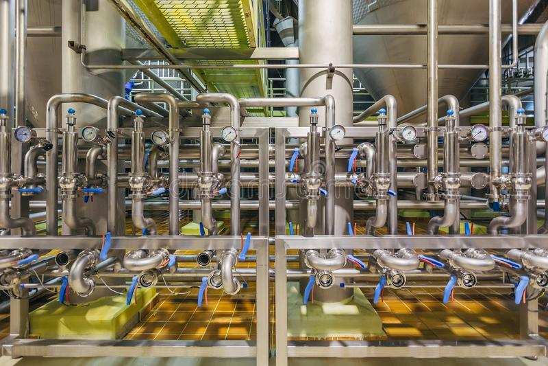 Intérieur moderne de brasserie Les tuyaux d'acier inoxydables industriels se sont reliés aux cuves et aux soupapes de commande photos stock