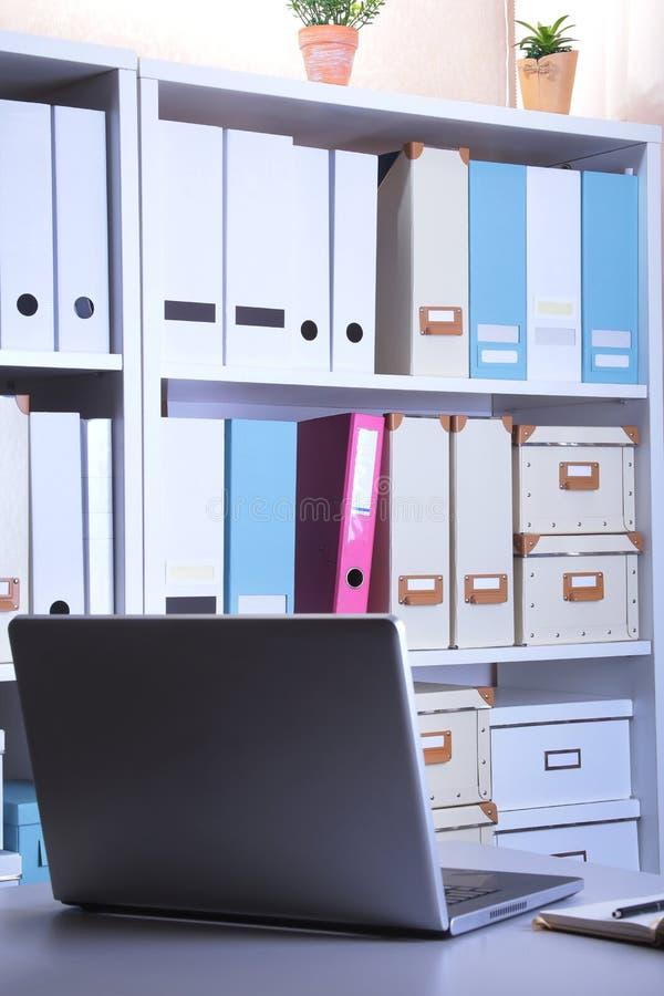 Intérieur moderne de bureau avec l'ordinateur portable, les chaises et les bibliothèques images libres de droits