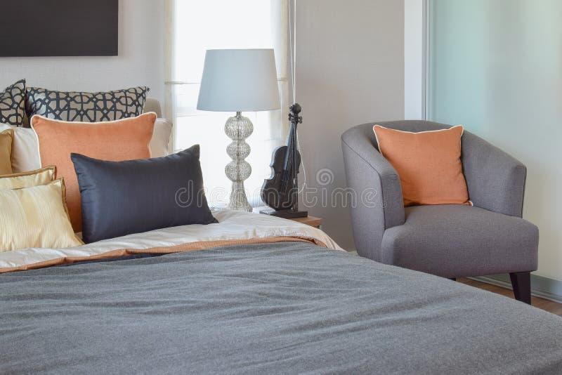 Intérieur moderne de chambre à coucher avec l'oreiller orange sur la lampe grise de table de chaise et de chevet photographie stock