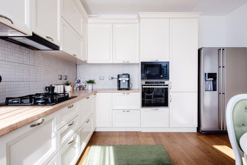 Intérieur moderne de cuisine avec des planchers en bois dur et des meubles crémeux blancs en bois photos libres de droits