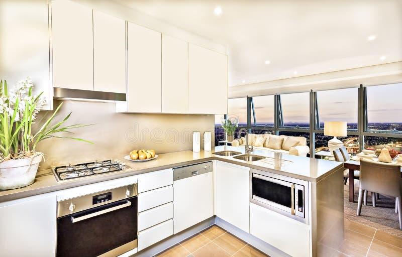 Intérieur moderne de cuisine avec le secteur de salon à la soirée photos stock