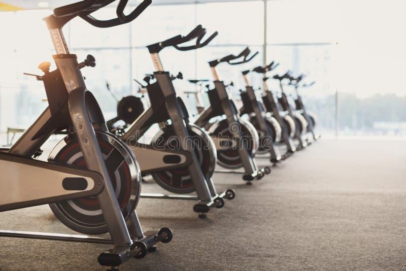 Intérieur moderne de gymnase avec l'équipement, vélos d'exercice de forme physique photos stock