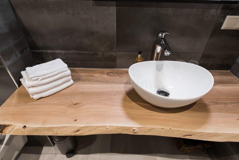 Intérieur moderne de la salle de bains Le lavabo est fait en coquille massive blanche sur la table du bois Minimalisme et photos libres de droits