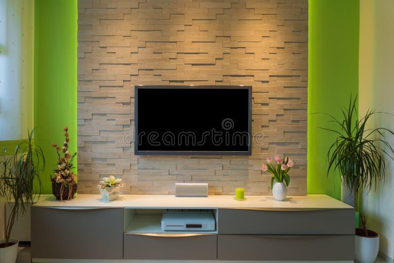 Intérieur moderne de salon - la TV a monté sur le mur de briques avec l'écran noir et la lumière ambiante photos stock